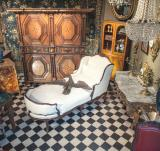 White chaise longue in a room full of antiques