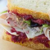 Close up of a Christmas sandwich with turkey, ham and cranberry sauce