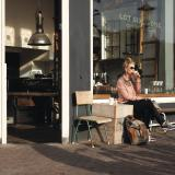 Woman sitting in the sun outside Lot Sixty One, drinking coffee
