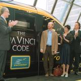 Some of the cast of the Da Vinci Code standing next to a wrapped train