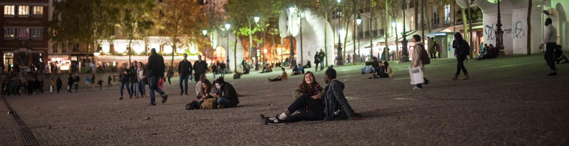 Couple sitting outside Beaubourg at night