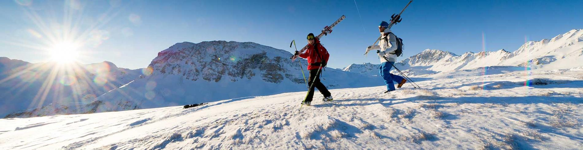 Man carrying his skis over his shoulder