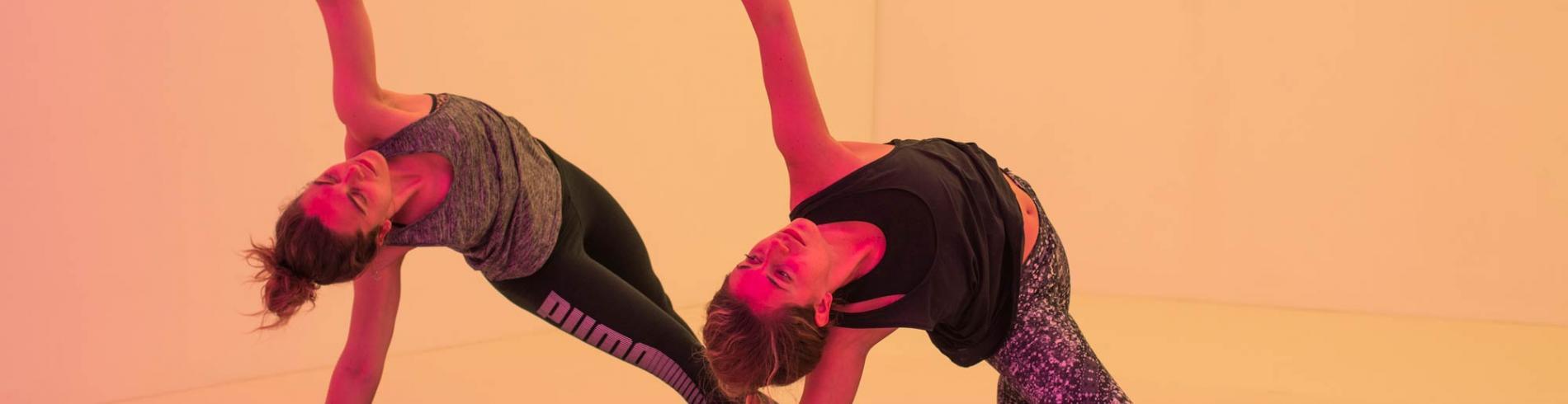 Two women practice yoga at Chroma Yoga