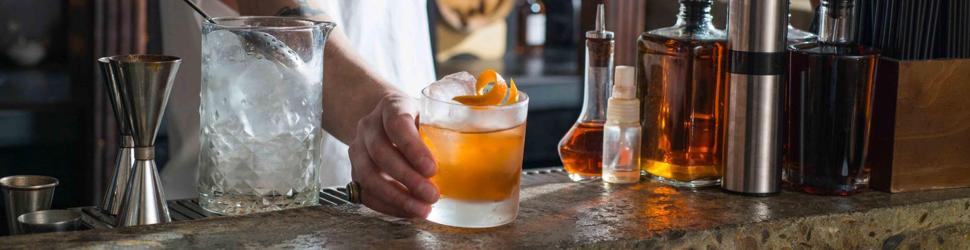 A bartender serves a cocktail at The Vault