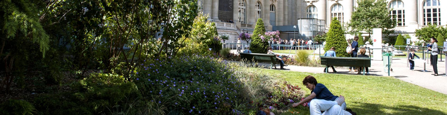 People sitting on the grass outside the Grand Palais