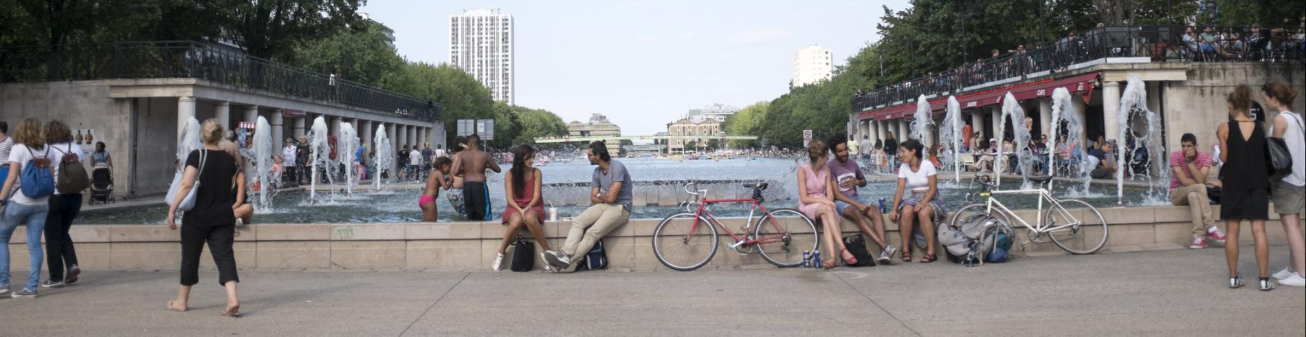 People sitting around a water feature in Parc de la Villette