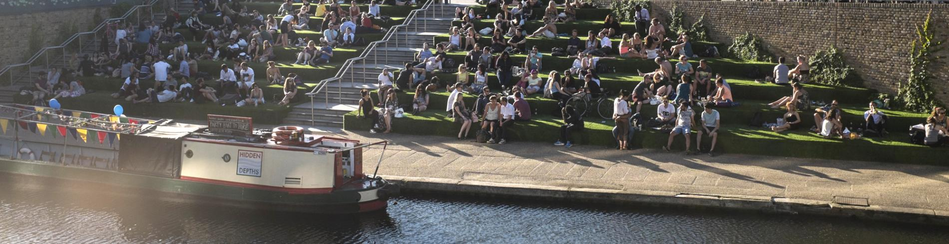 People sitting on the steps down to the canal at Granary Square