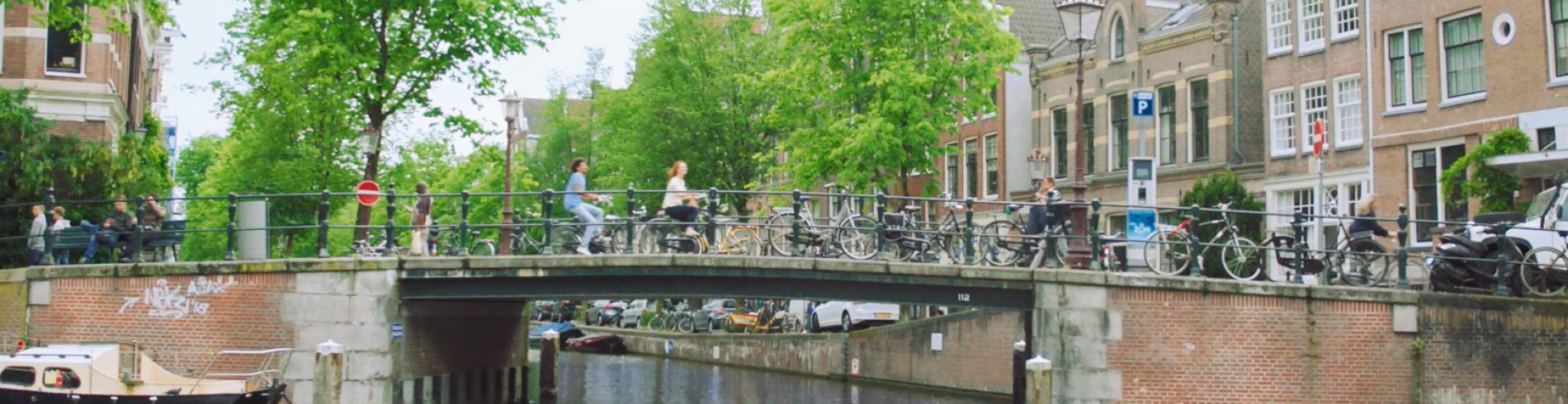 Couple riding bikes across a bridge in the sun