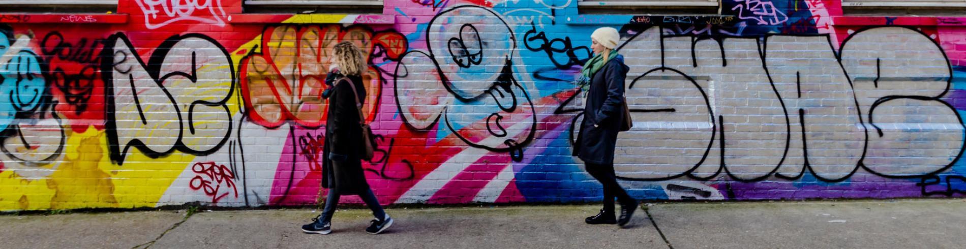 Two women walking past a graffiti covered wall