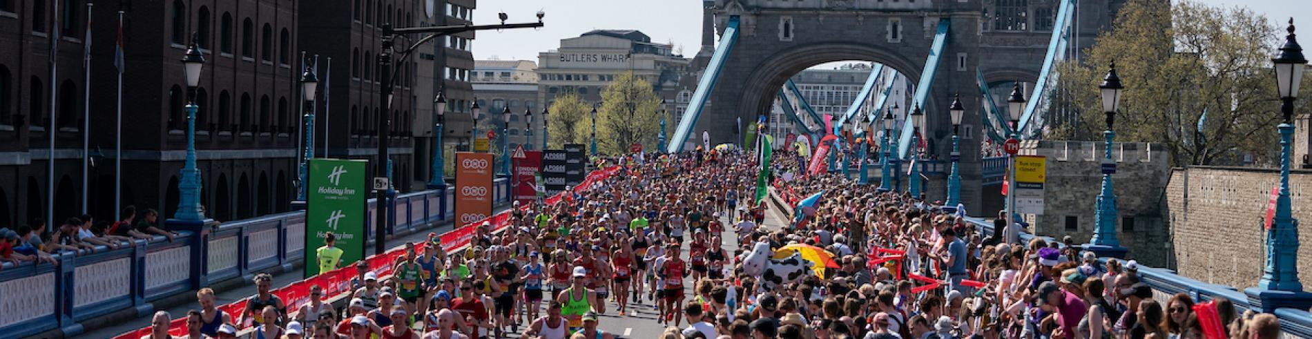 Toeschouwers en deelnemers aan de London Marathon met Tower Bridge op de achtergrond
