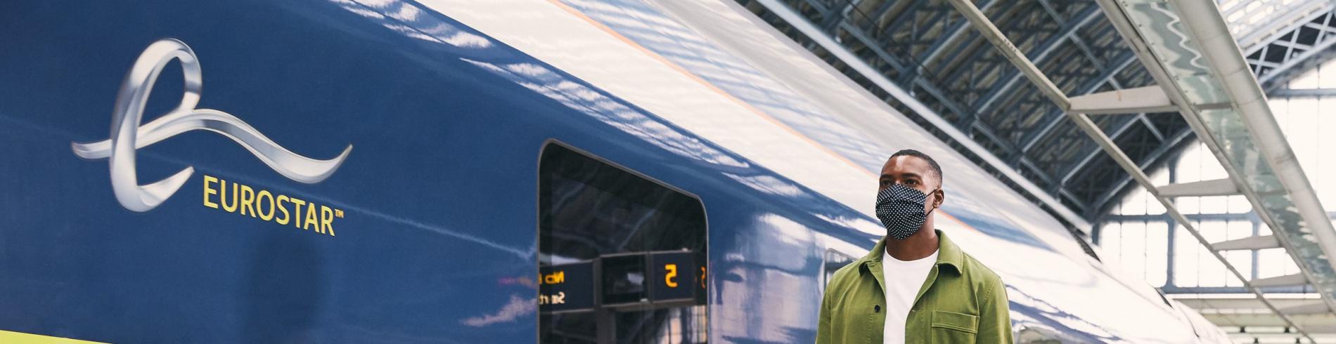 Man in mask getting on the Eurostar train