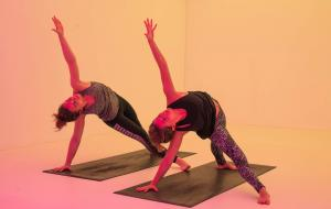 Two women practice yoga at Chroma Yoga