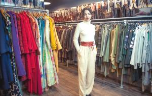 Sylvie Chateigner standing in her shop surrounded by vintage clothes