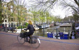 Woman cycling across a bridge over a canal with spring growth starting on the trees