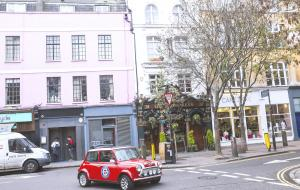 Red Mini driving through the street in Covent Garden