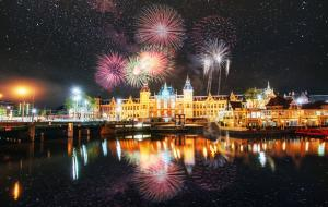 Fireworks over Centraal Station with reflections in the water