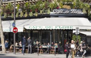 People sitting outside on the terrace of the cafe de Flore in St Germain des Pres