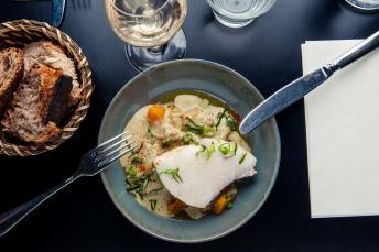 White fish in a creamy sauce, garnished with spring onions
