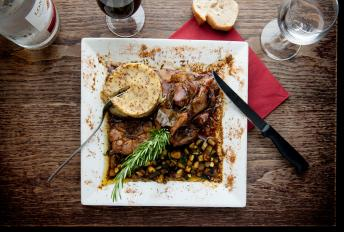 Hearty meat stew served with mustard mash and garnished with a sprig of rosemary