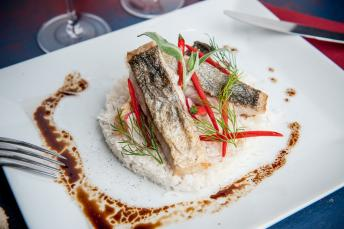 Fish dish served on a bed of rice and garnished with fresh herbs