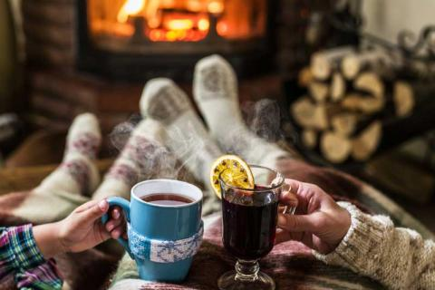couple sitting in front of a fire having a hot drink in Courchevel