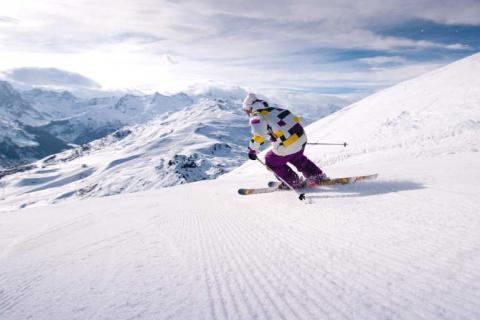 Skier in magenta trousers skiing down the slopes