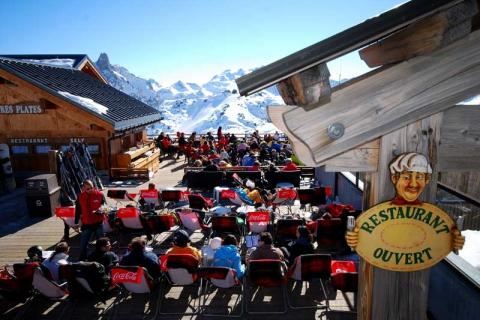 People sitting in an open-air restaurant on the slopes eating