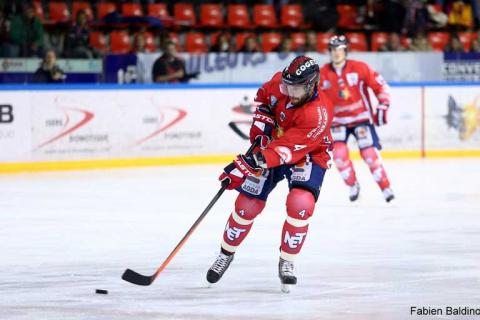 Players in red playing ice hockey