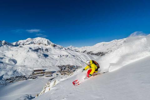 Skier in yellow skiing down a slope