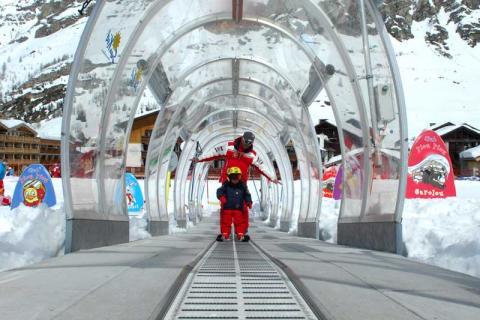 Children skiing through a glass tunnel