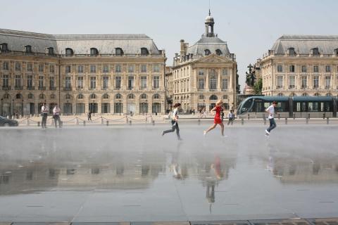 Children playing in the Miroir d'eau along the riverfront in Bordeaux