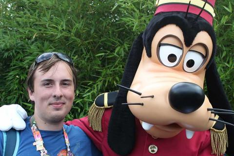 Geoff standing with his arm around Pluto at Disneyland Paris