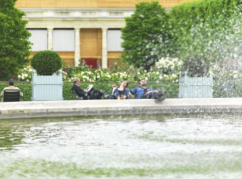 Couple sitting by a fountain in the park with their feet up