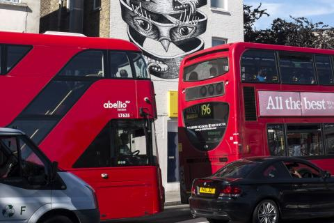 Red London buses back to back in traffic