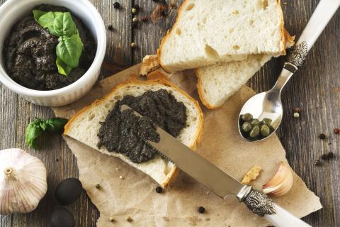 Black tapenade olive paste on a slice of crusty white bread
