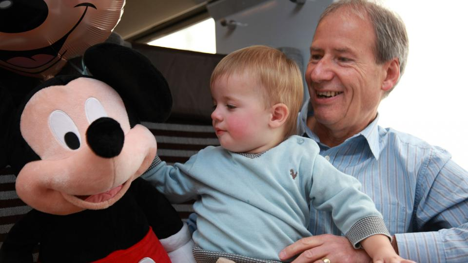 Grandfather and child on board the Eurostar Disney train with a Mickey Mouse soft toy