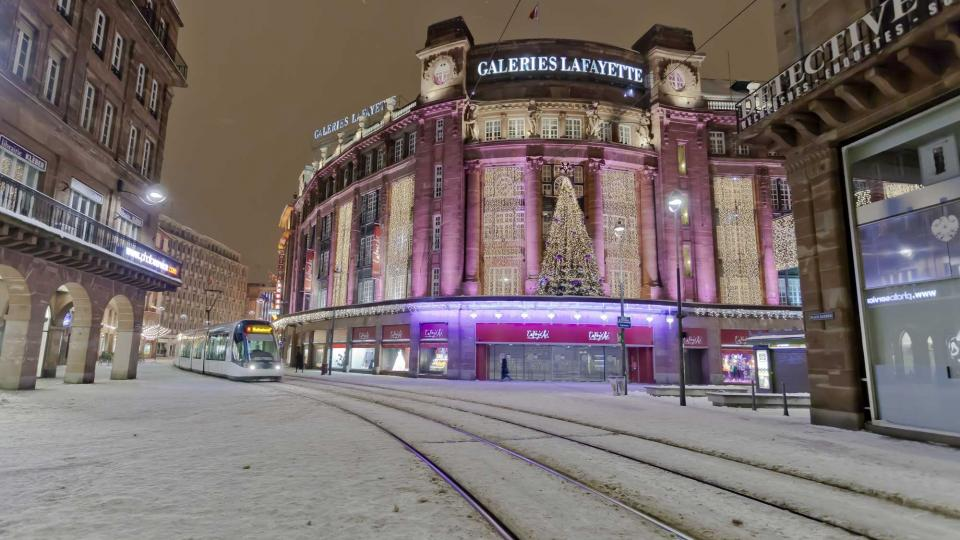 A tram passing through the shopping district on a snowy winter's evening in Strasbourg