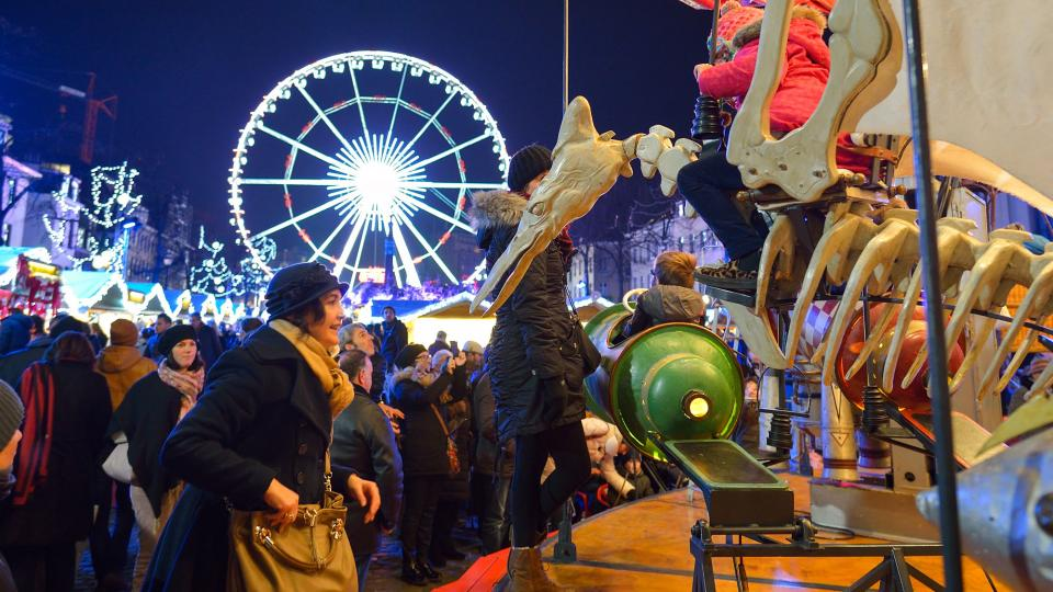 Mother watching her children on a merry go round at Brussels Christmas market with the big wheel in the background