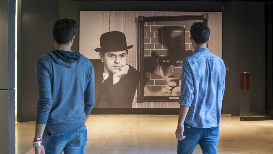 Two men standing looking at one of the paintings in the Magritte Museum